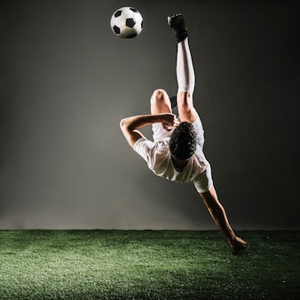 Faceless sportsman falling and kicking ball