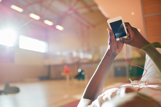 スマートフォンを使用して顔のないスポーツマン