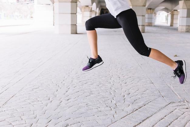 Faceless sportswoman leaping