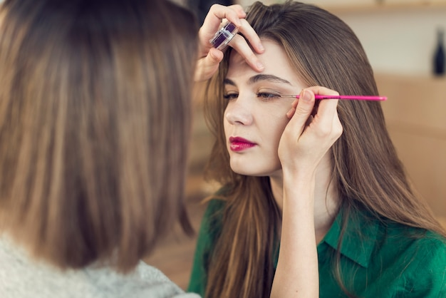 Faceless stylist applying eyeliner on model