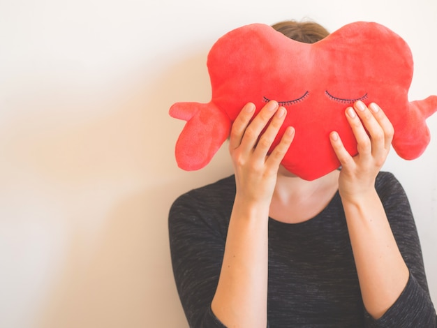 Faceless woman covering face with red heart toy