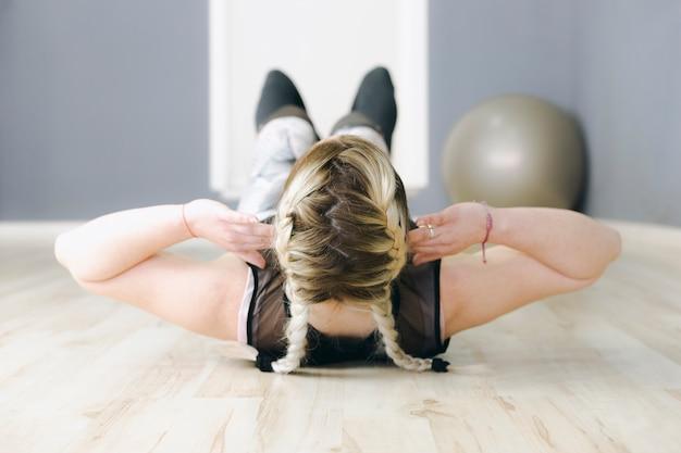 Donna anonima che si esercita sul pavimento