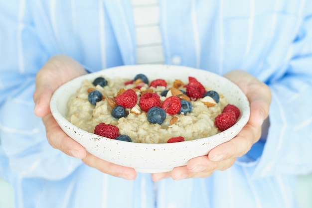 Faceless woman holds in hands breakfast, oatmeal porridge with berries and nuts