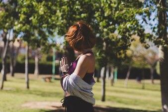 Faceless woman meditating in park