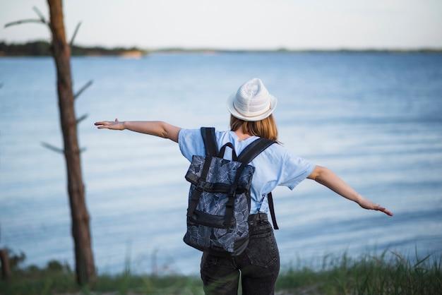 Faceless woman walking towards lake