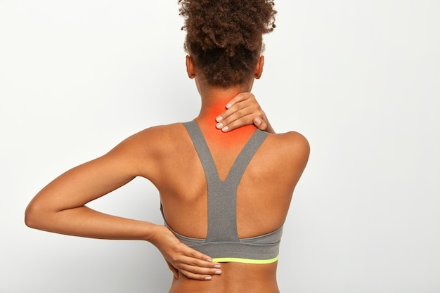 어두운 피부를 가진 익명의 여자는 목덜미 통증으로 고통 받고, 붉은 반점으로 목에 손을 잡고, 건강, 척추 질환에 문제가 있으며, 흰색 배경 위에 절연 된 스포츠 브래지어를 착용합니다. 통증 증후군