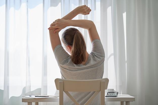 Безликая молодая женщина, работающая из дома и испытывающая дискомфорт из-за проблем с удаленной работой