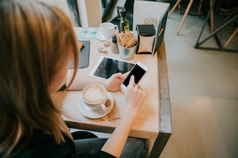 Faceless young woman browsing smartphone in cafe