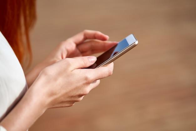 顔の見えない若い女性がスマートフォンを押しながら入力
