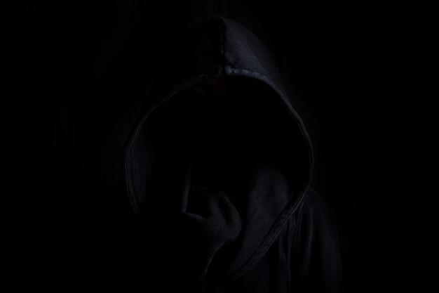 검은 배경에 어둠 속에서 검은 가운을 입고 얼굴이 보이지 않습니다.