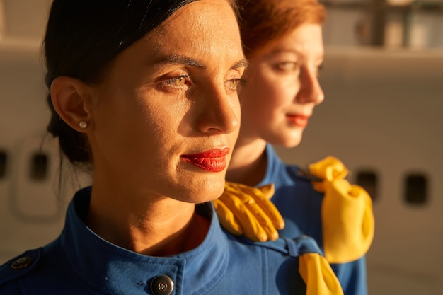 Faces of two calm attractive flight attendants standing in the sunset light and looking into the distance