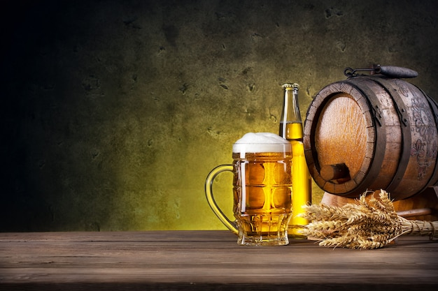 Faceted glass of beer, bottle and barrel