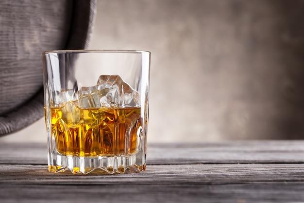 ウイスキーの多面的なガラスと木製の樽の角度