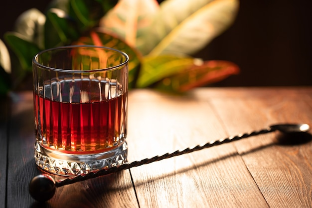 Faceted glass of whiskey on a wooden table against the background of exotic plants