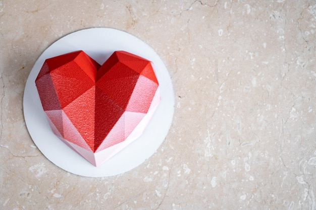 Faceted red heart mousse cake with velor coating on a soft pink marble table