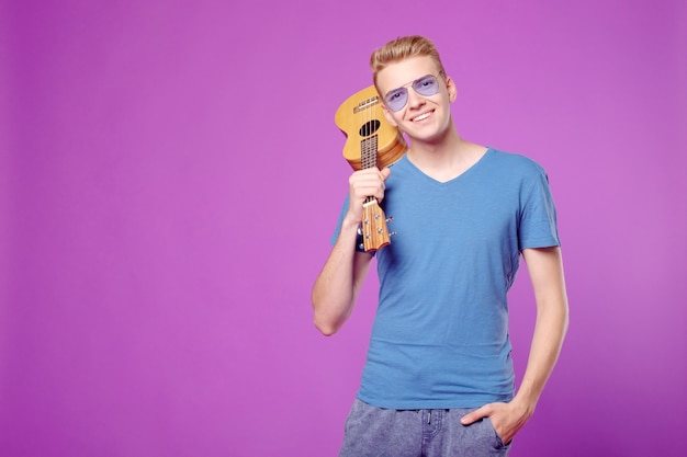 Fachion beauty funny man with ukulele in hands on purple background copyspace
