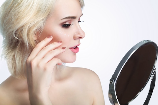 フェイシャルビューティー。屋内の鏡で見ている新鮮な健康な肌を持つセクシーな若い女性の肖像画。顔に触れる自然なメイクで美しい笑顔の女の子のクローズアップ。化粧品の概念。