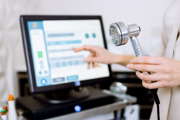 얼굴 미용 치료. led 빛 치료를위한 도구를 들고 전문 여성 미용사의 손의 이미지를 자른