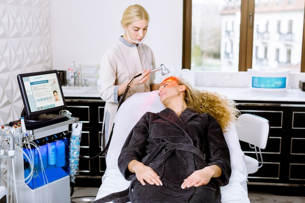 현대 미용 클리닉의 얼굴 미용 치료. 빨간 led 빛 치료하는 데 꽤 금발 곱슬 여자