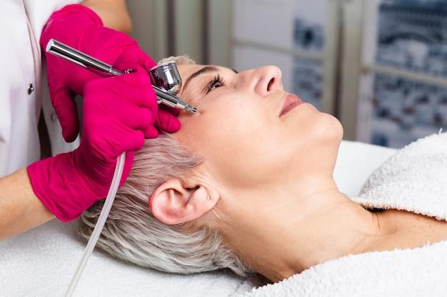 미용 미용실에서 산소 표피가 벗겨진 아름다운 노년 여성의 얼굴 미용 치료.