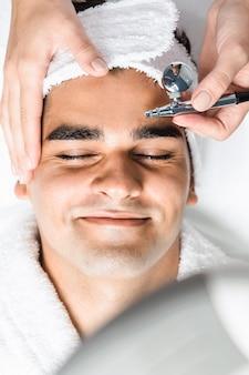 미용 미용실에서 산소 표피가 벗겨진 잘 생긴 남자의 얼굴 미용 치료.