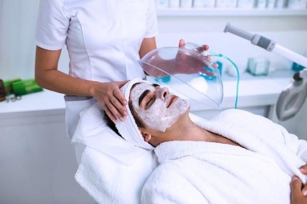 미용 미용실에서 산소 마스크를 쓴 잘 생긴 남자의 얼굴 미용 치료.