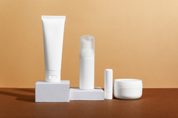 Facial and body care cosmetics bottles composition on brown background.