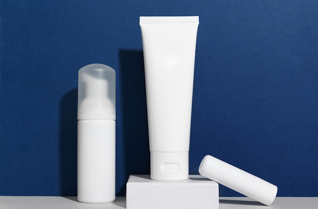 Facial and body care cosmetics bottles composition on classic blue background.