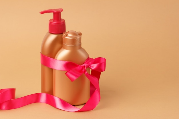Facial, body skin care on beach, sea on summer vacation. set for safe tan with pink satin ribbon on bronze background. copyspace.