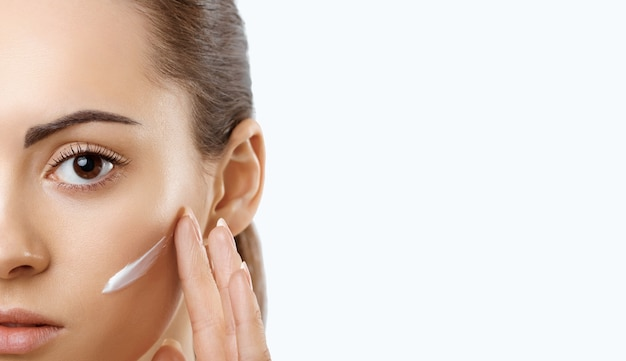 Facial care female applying creamportrait of  young woman with cosmetic cream on skin