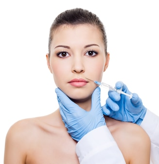 Facial care.  injection of botox in beautiful woman's face  isolated white