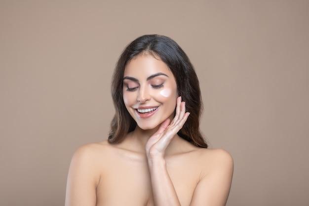 フェイシャルケア。顔にクリーム色の長い黒髪と優れた構造の垂れ下がったまぶたを持つきれいな女性。