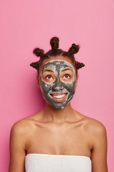 フェイシャルクリーニング、スキンケア、美容トリートメントのコンセプト。喜んで暗い肌の女性は喜びで上を見て、シャワーを浴びた後、タオルに包まれた若返りスタンドに粘土栄養マスクを適用します