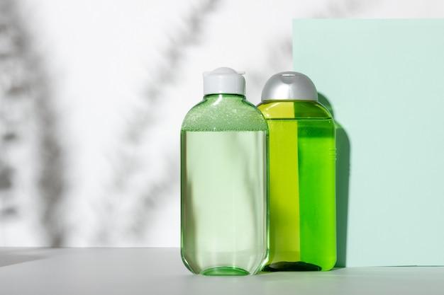 페이셜 클렌저 병. 식물 가지의 거친 그림자가 있는 흰색 배경에 얼굴을 정화하기 위한 로션이나 균사체. 녹색 포장의 액체 화장품. 천연화장품