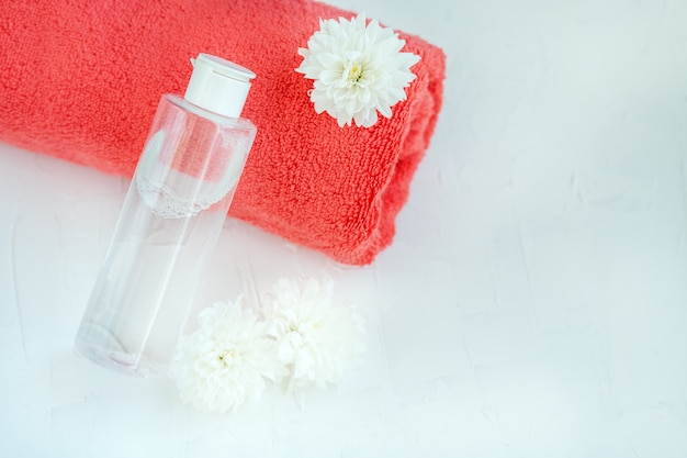 Facial cosmetic and towel on a white background. the concept of