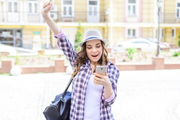 Эмоции на лице, выражающие чат-соединение, роуминг интернет-концепция хороших новостей. портрет довольно красивой радостной веселой ликованной дамы, поднимающей руки вверх, глядя на телефон в руках, получающих отправку sms