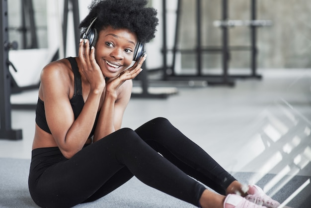 Facial expression. african american woman with curly hair and in sportive clothes have fitness day in the gym