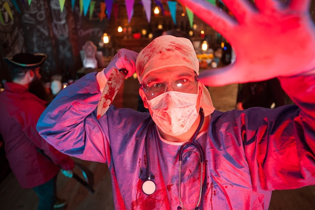 Facial expression of creepy man dressed up like a doctor holding a knife at halloween party. halloween party in a night club.