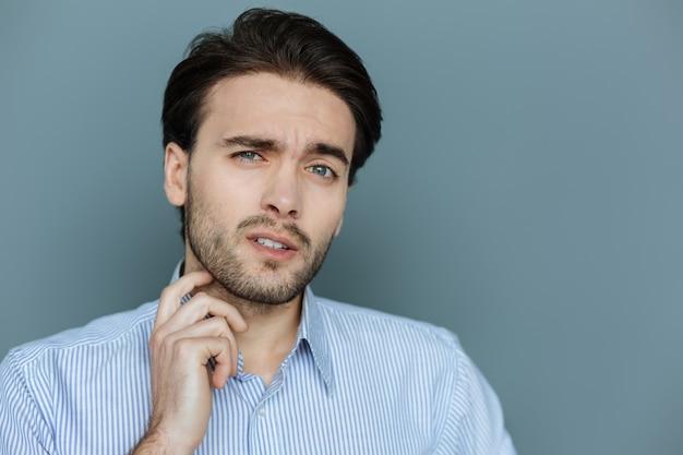 表情。彼のひげに触れながらあなたを見ている素敵な快適なハンサムな男の肖像画