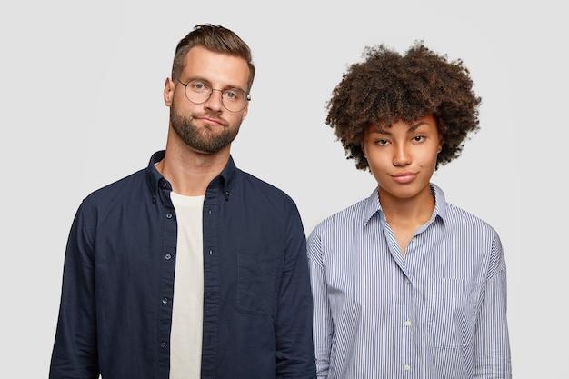 Концепция выражения лица и эмоций. горизонтальный вид озадаченных женщины и мужчины смешанной расы с недовольными серьезными взглядами