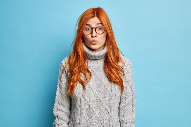 Concetto di espressioni facciali. la bella donna europea dai capelli rossi tiene le labbra piegate e sembra sorprendentemente che indossa un maglione lavorato a maglia.