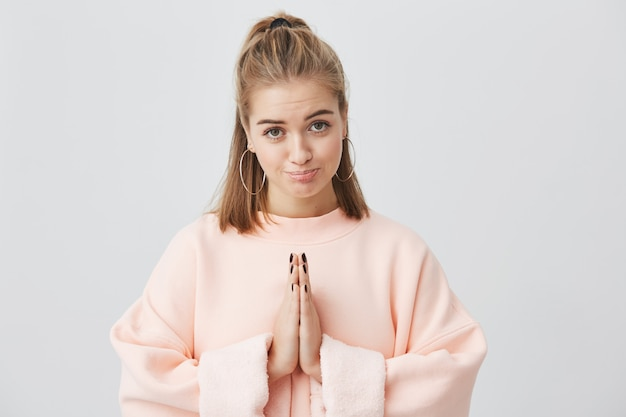 Выражения лица, эмоции, язык тела. симпатичная очаровательная девушка, одетая в розовое, сжимающая ладони перед собой, с сожалением и сожалением смотрит, прося прощения.