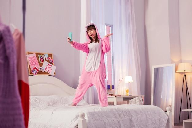 Выражения лица. положительно обрадованная девушка смотрит в камеру и прыгает на кровати