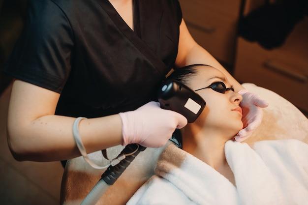Процедура удаления волос на лице брюнетке с использованием современного аппарата в спа-салоне