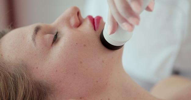 안면 리프팅, 주름 스무딩 및 라이타이드 소실 절차. 미용사는 여성의 얼굴에 조작자를 움직입니다. 미용 및 spa 개념입니다.