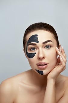 Маска для лица. красивая молодая женщина с черной маской глины на стороне. забота кожи. модель девушки с косметической маской. уход за лицом. увлажняющая маска spa