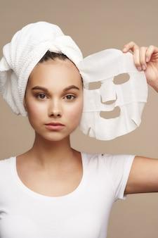 그녀의 머리 베이지 색에 수건으로 흰색 티셔츠에 페이셜 마스크 깨끗한 피부 회춘 스파 절차 미용 여자