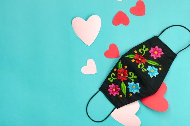ハートの青い背景に花で飾られたフェイシャルマスク。バレンタインデーの背景。
