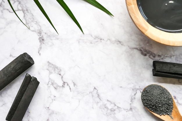 Facial mask and scrub by activated charcoal powder on marble table.