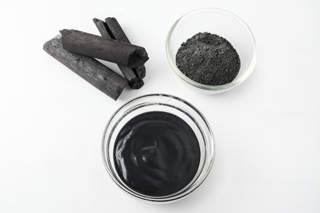Facial mask and scrub by activated charcoal powder on white background